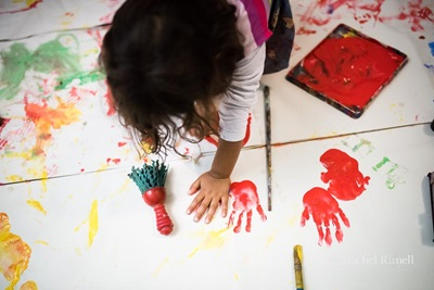 Birds-eye view of child making hand prints with paint.