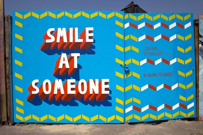 Light blue wall with orange type that says 'smile at someone'